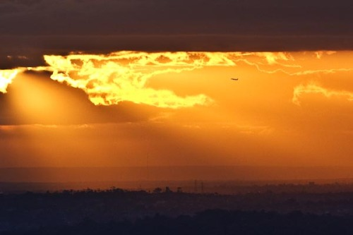 Can you see the aircraft flying into the sunset after having just taken off from the Melbourne airport.